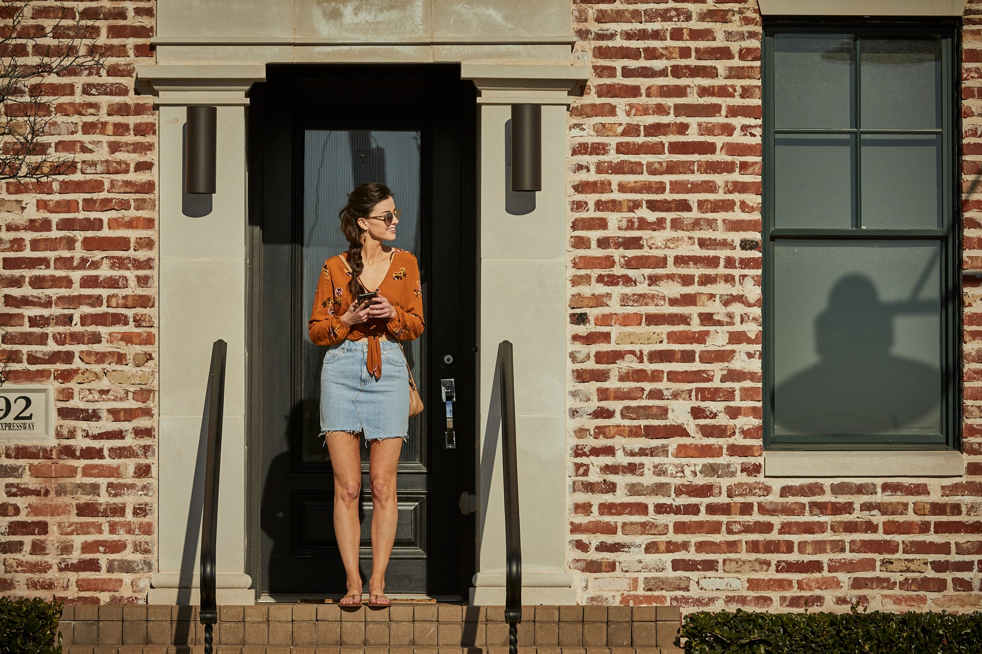 Woman stands at the top of the stairs to her Brownstone, wearing a denim skirt, an orange tie-fornt top, tan leather flip flops, and sunglasses. She's holding her phone and looking over her left shoulder, smiling.