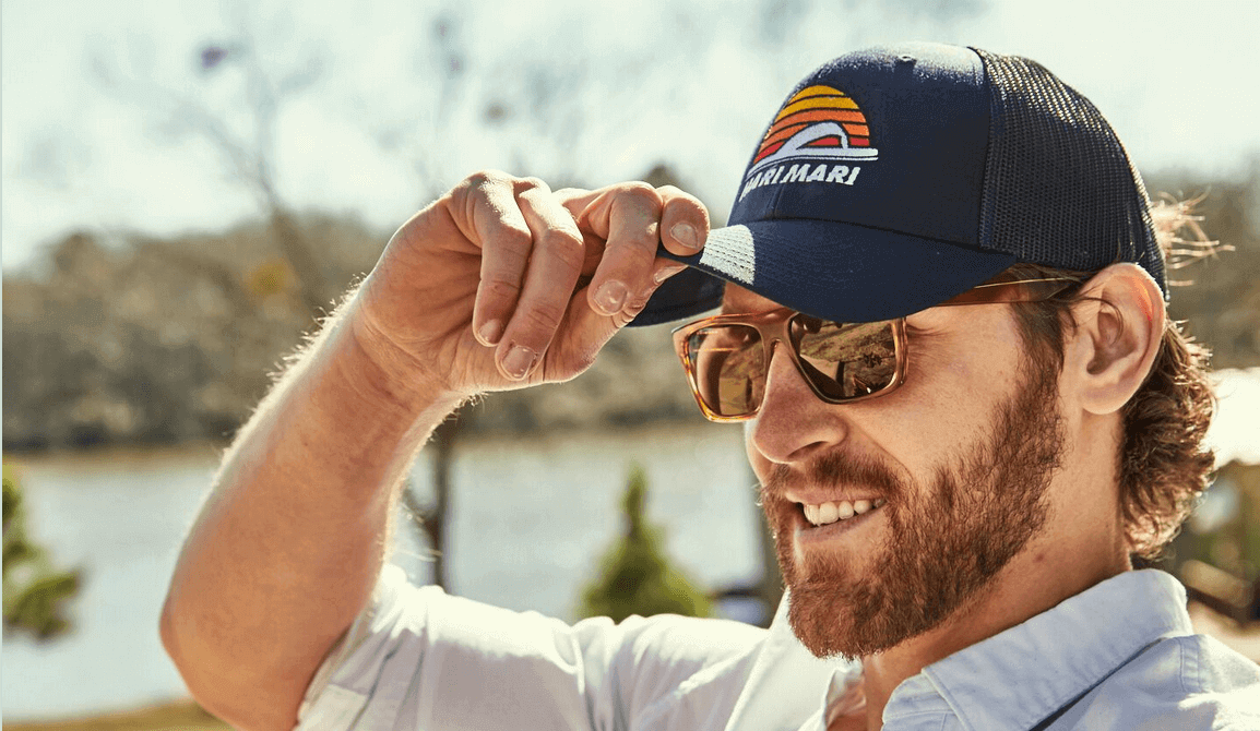 a bearded man wearing sunglasses smiles into the distance with a lake behind him as he holds the brim of his Hari Mari Navy Trucker hat