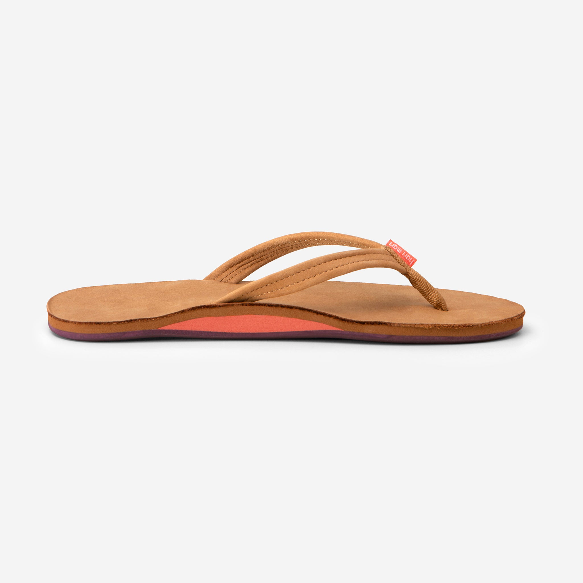 side profile of Hari Mari Women's fields flip flops in tan/fig on white background