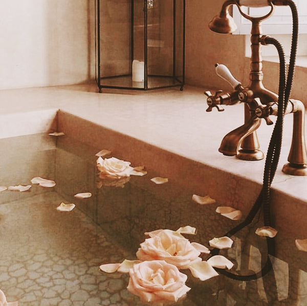 Modern Moroccan bathroom made of traditional materials with roses and a candle holder in the background