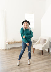 Our teal, pom pom sleeve sweater paired with jeans.
