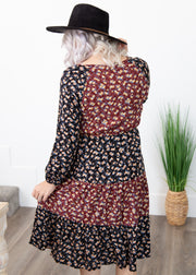 Amelia is wearing our black and burgundy mix floral pattern dress paired with a black hat and heeled booties!