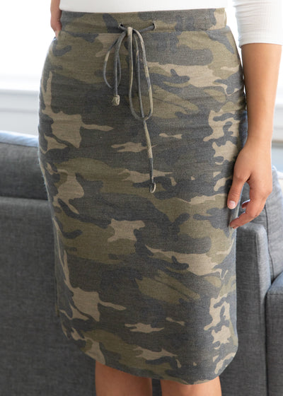 Nichole is wearing our camouflage skirt paired with a white top and chunky heels.