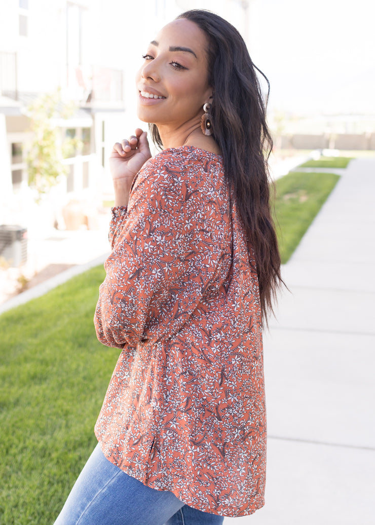 Our rust, floral long sleeve blouse paired with jeans.