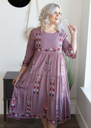 Amelia is wearing our lavender, embroidered, tiered style dress paired with heeled booties!