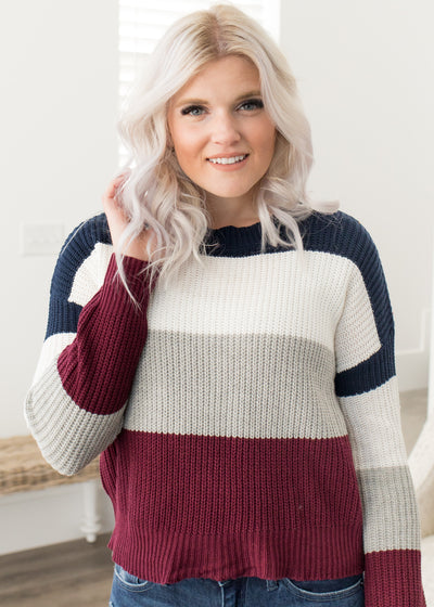 Our navy and burgundy color block sweater paired with jeans.