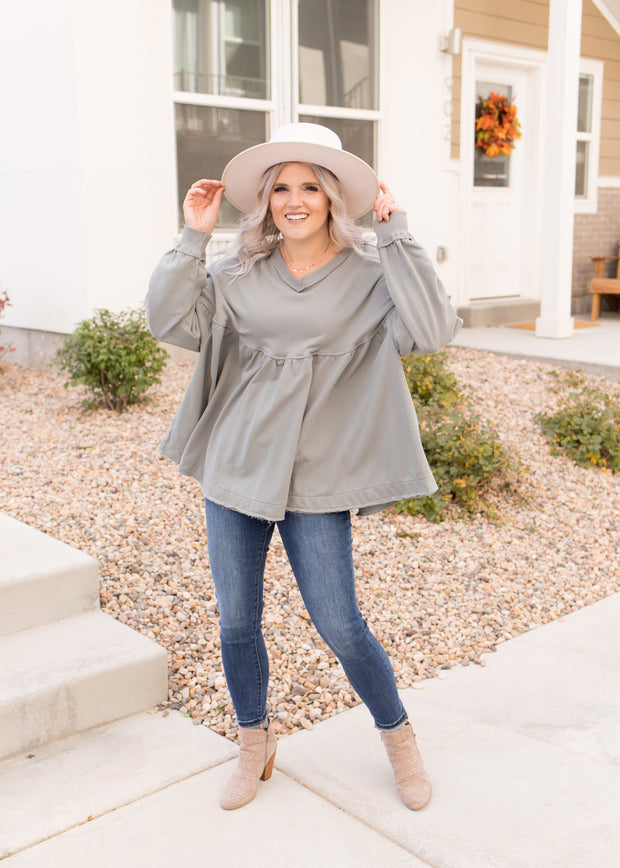 Our sage-blue, raw hem peplum top paired with jeans.