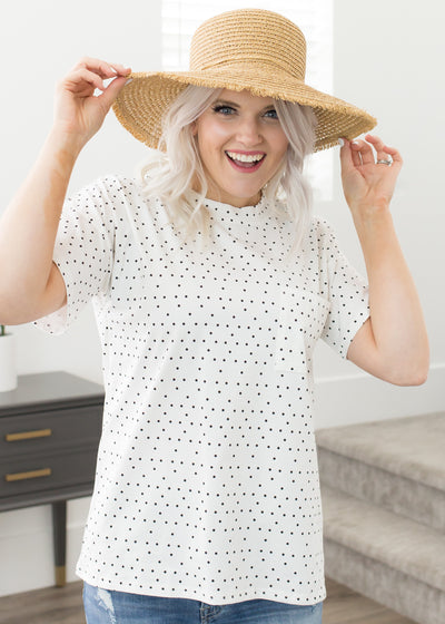 Amelia is wearing our white and black polka dot top paired with shorts, a hat and sandals.