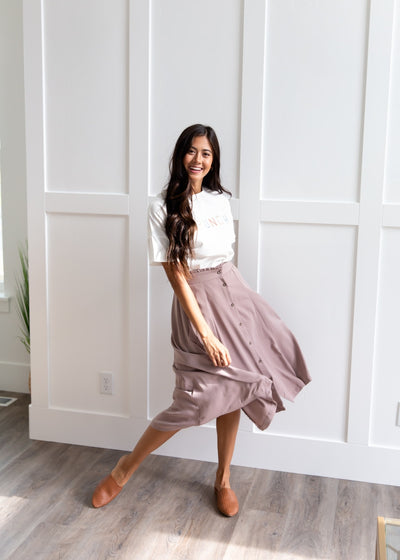 Vanessa is wearing our taupe, button down skirt paired with a white top and tan flats.