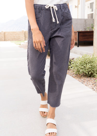 Our dark, charcoal pinstripe linen pants paired with white sandals.