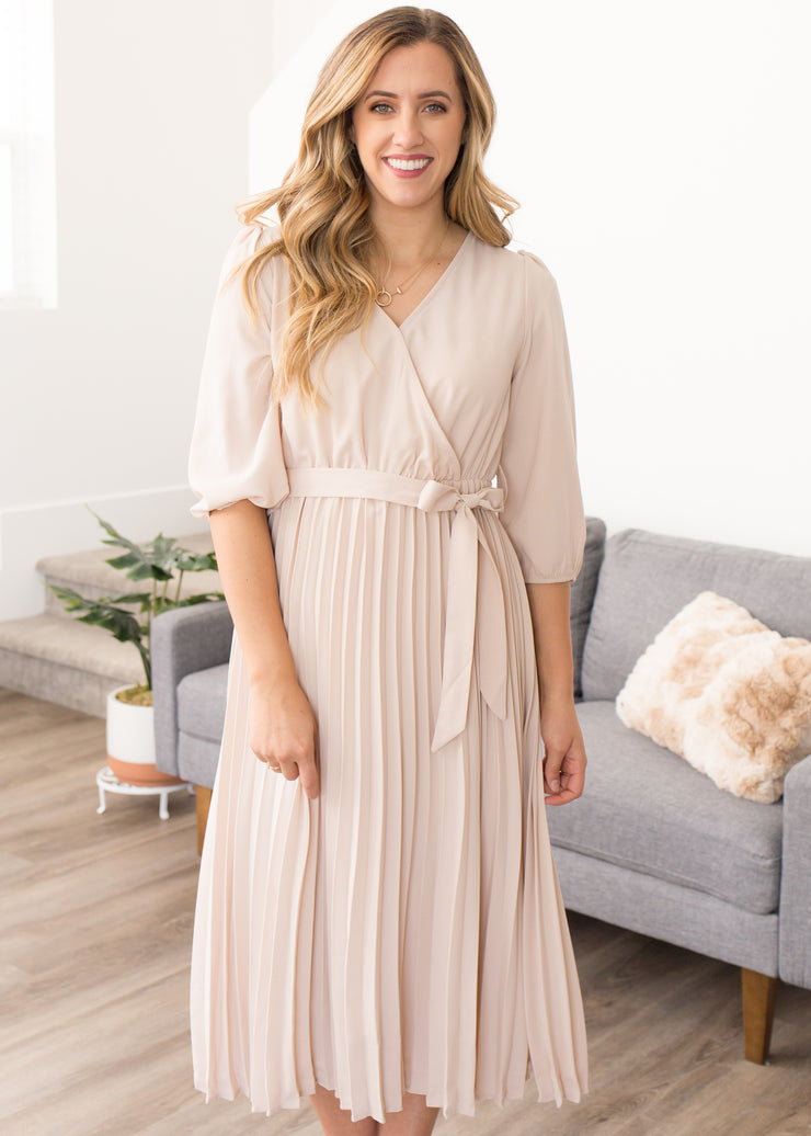 Nichole is wearing our cream, wrap neck, pleated dress paired with heels.