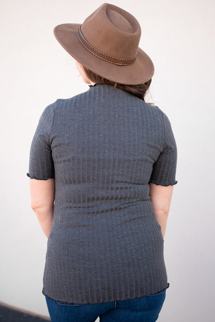 Janelle is wearing our charcoal ribbed, mock neck top paired with skinny jeans, flats and a hat!