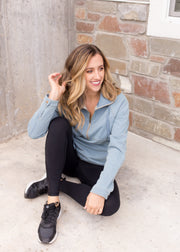 Nichole is wearing our dusty blue, half zipper jacket paired with black leggings and sneakers.