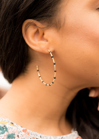 Black and gold beaded hoop earrings.