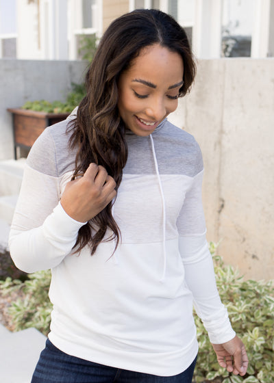 Our oatmeal, grey and white colorblock hoodie paired with jeans.