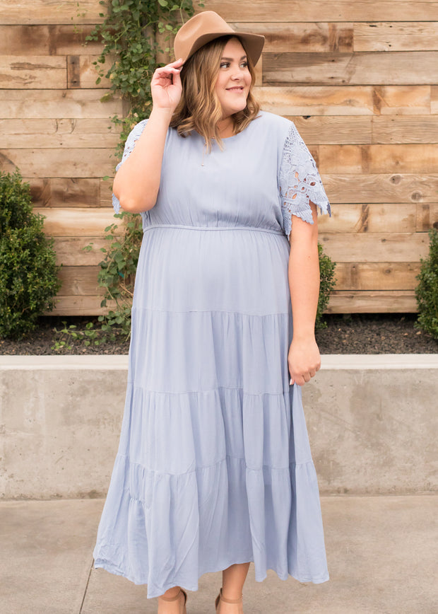Kira is wearing our dusty blue, tiered lace sleeve maxi dress.
