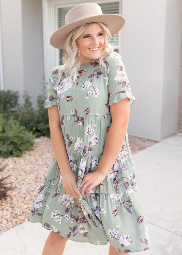 Our sage, floral, tiered style dress paired with a hat.