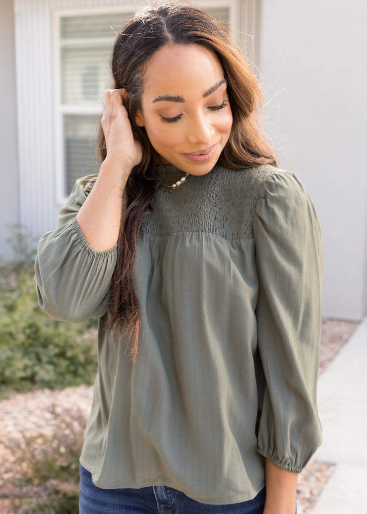 Our olive, smock bib top paired with jeans.