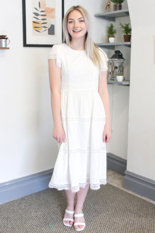 Kenzie is wearing our white, eyelet lace dress paired with sandals.