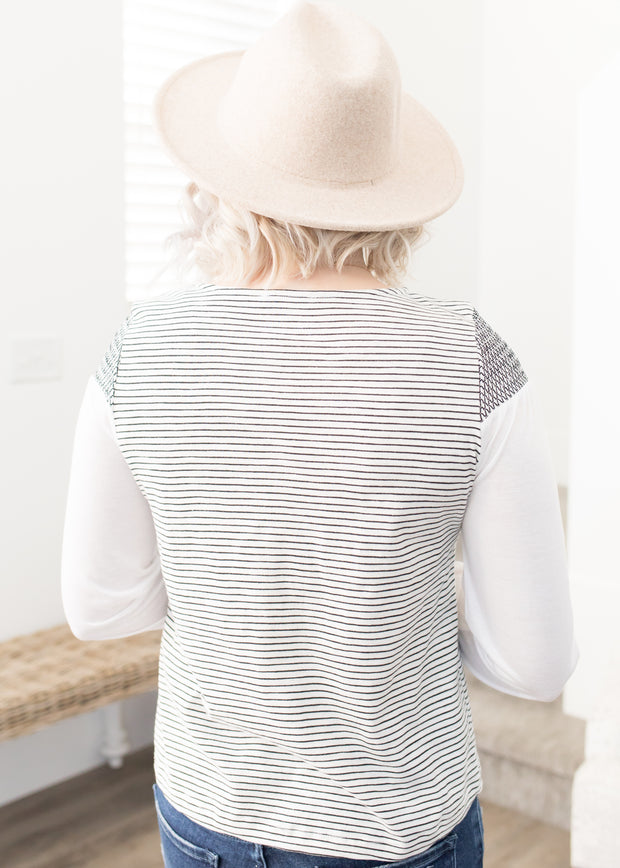 our black and white stripe, white sleeve top paired with jeans.