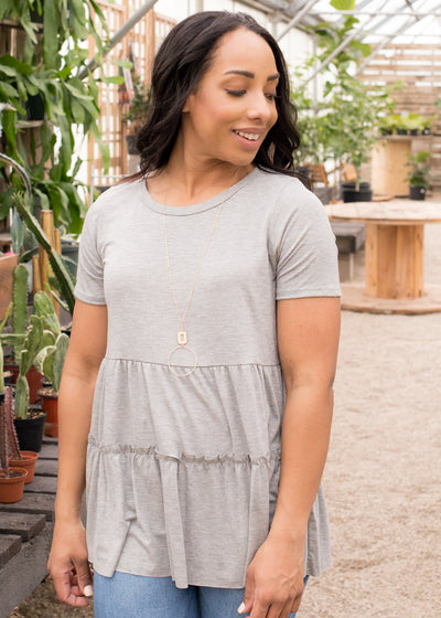 Vanessa is wearing our light grey, peplum tiered top paired with jeans.