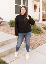 Our black, zipper back detail plus size sweatshirt paired with jeans.