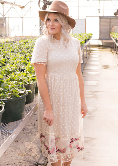 Amelia is wearing our sheer overlay, embroidered dress paired with heels and a hat.