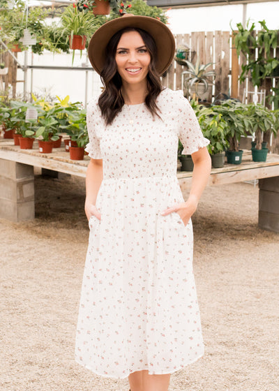 Janelle is wearing our ivory floral dress paired with heels and a hat.