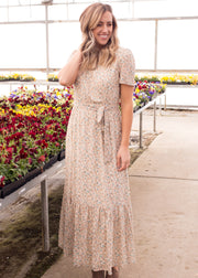 Nichole is wearing our ivory, floral wrap maxi dress with heels.