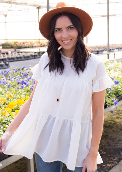 Janelle is wearing our white, tiered style blouse paired with jeans, booties and a hat.