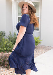 Our navy, embroidered plus size midi style dress paired with heels.