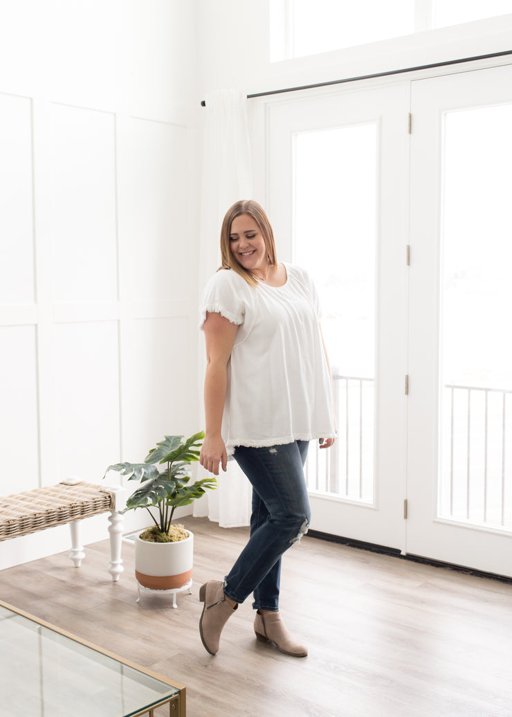Kira is wearing our white, fringe ruffle trim top paired with jeans and booties.