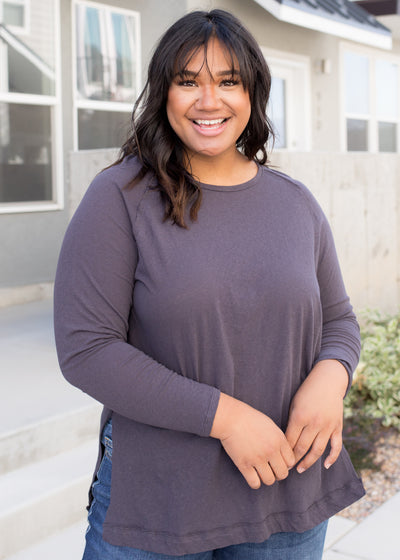 Our charcoal plus size, raw hem top paired with jeans.
