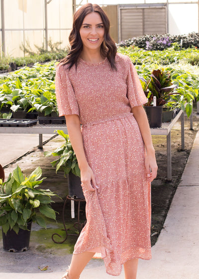 Janelle is wearing our blush floral, tiered style dress paired with heels.