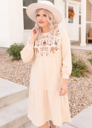 Our cream, embroidered tier style dress paired with a hat.