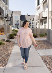 Plus size, coral and white stripe tie sleeve top paired with jeans.
