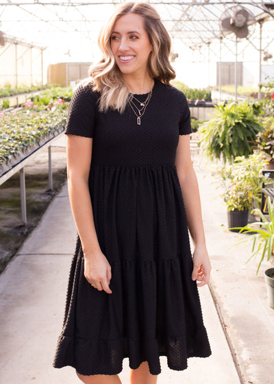 Nichole is wearing our black, swiss dot textured dress paired with chunky heels.