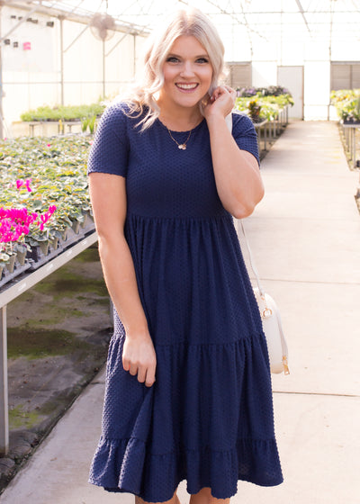 Amelia is wearing our navy, swiss dot textured dress paired with heels.