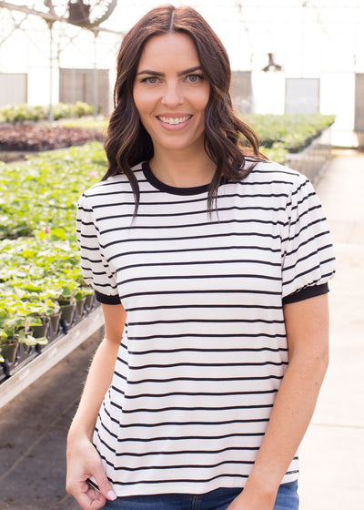 Janelle is wearing our white and black striped top paired with jeans and flats.