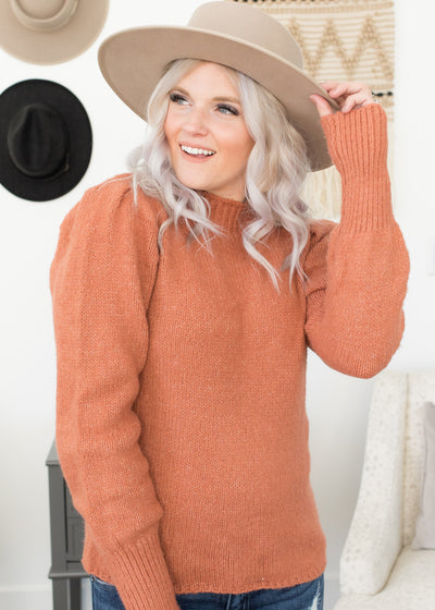 Our rust, puff sleeve sweater paired with jeans.