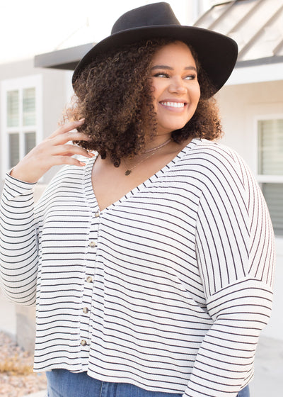 Our white and black stripe functioning button down top paired with jeans.