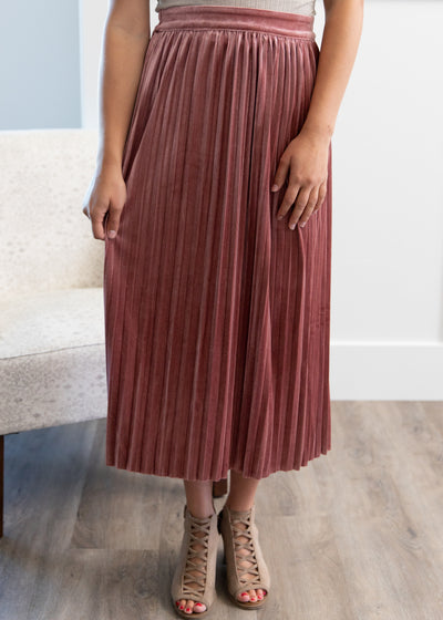 Nichole is wearing our mauve, velvet, pleated midi skirt paired with a bell sleeve top and chunky heels!