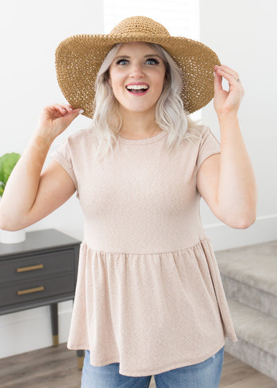 Amelia is wearing our taupe peplum top paired with shorts, sandals and a hat.