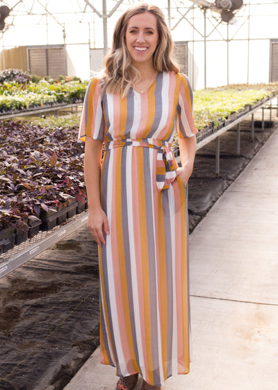 Nichole is wearing our colorful stripe maxi dress paired with heels.