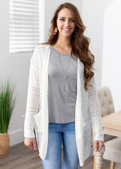 lexi is wearing our white crochet style cardigan paired with a grey t-shirt, skinny jeans and booties!