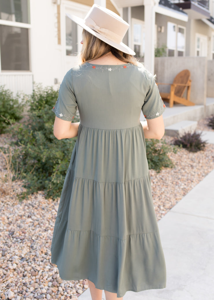 Our sage green, embroidered dress paired with heels.