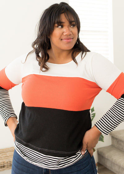 Our burnt orange, color block and stripe plus size top paired with jeans.