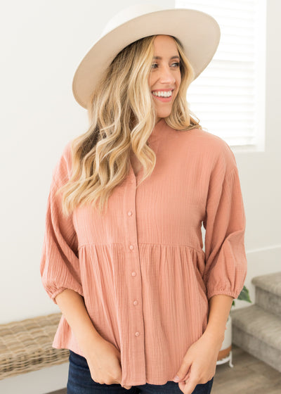 Our peach, button down babydoll collared top paired with jeans.