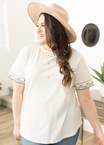 Our white, plus size embroidered sleeve top paired with jeans.
