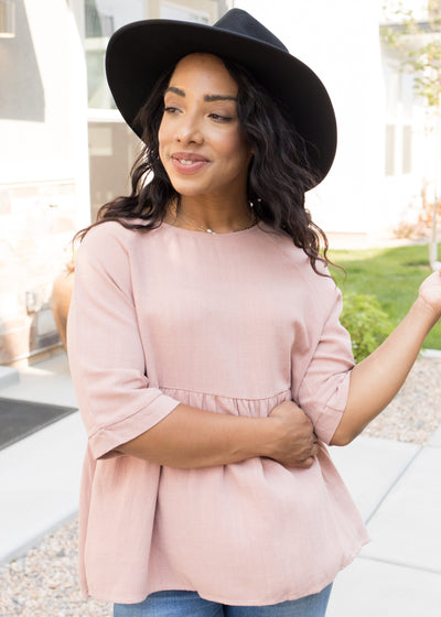 Our blush, peplum top paired with jeans.